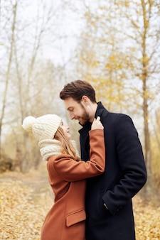 Liebespaar zu fuß in park im herbst umarmungen und küsse. herbstwegmänner und -frauen im wald auf den gefallenen blättern. romantik und liebe auf einer herbstlandschaft