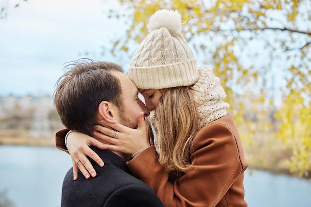 Liebespaar zu fuß in park im herbst umarmungen und küsse.