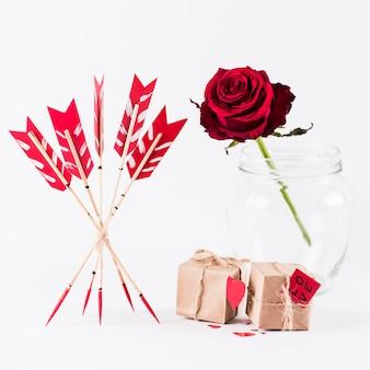 Liebespfeile mit geschenkboxen und rotrose