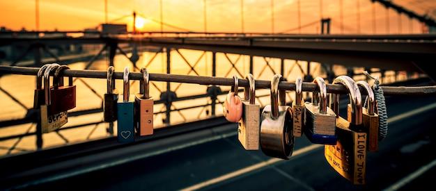 Liebesschlösser auf der brooklyn bridge, new york, mit sonnenaufgang im hintergrund.