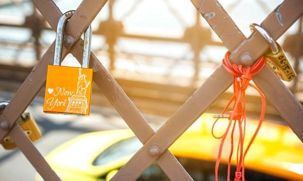 Liebesschloss mit freiheitsstatue im brückenraster mit gelbem taxi, das im hintergrund die straße hinuntergeht