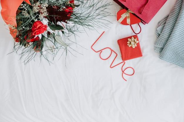 Liebesschreiben in der nähe von geschenken und blumen
