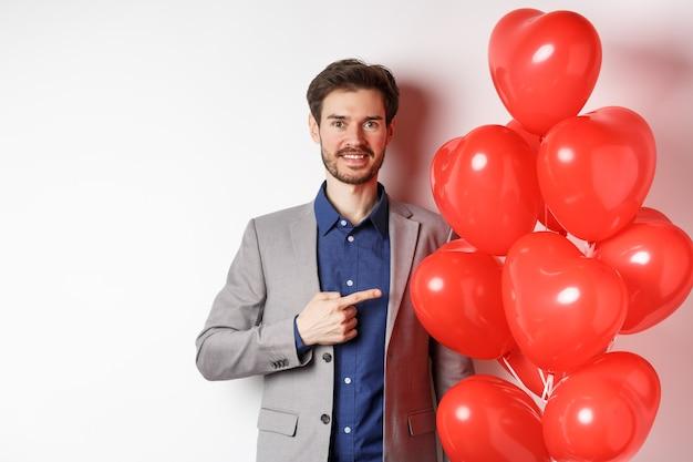 Liebestag. hübscher lächelnder kerl im anzug, der überraschungsgeschenk am valentinstag datiert, auf romantische herzballons zeigt und glücklich schaut, über weißem hintergrund stehend.