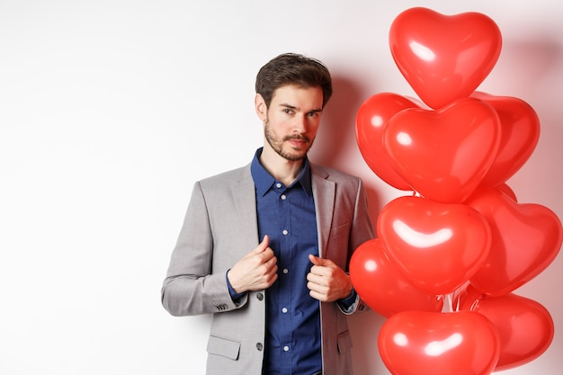 Liebestag. hübscher und selbstbewusster junger mann, der sich für valentinstag anzieht, anzug repariert und kamera betrachtet, nahe romantischen herzballons stehend, weißer hintergrund.