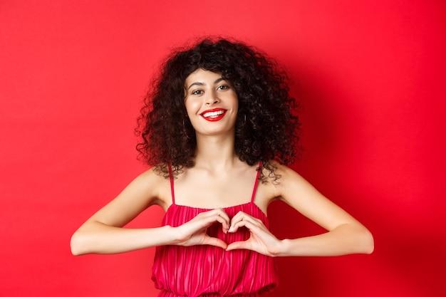 Liebestag. schöne frau, die valentinsgrüße feiert, herzzeichen zeigend und lächelnd, im romantischen roten kleid auf studiohintergrund stehend.
