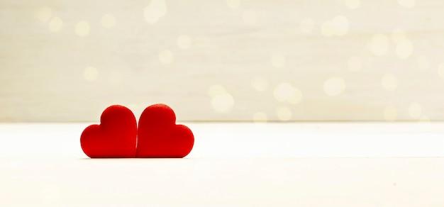Liebestag, valentinstaghintergrund, zwei rote herzen auf hölzernem hintergrund mit goldenem bokeh. bannergröße. speicherplatz kopieren.