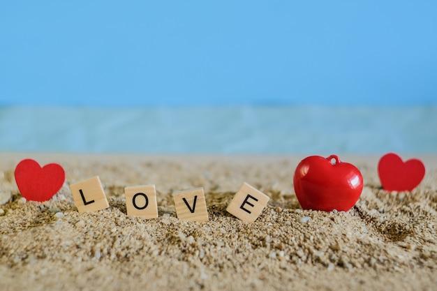 Liebestext auf holz mit tropischem sandstrand, liebeskonzept und weichzeichner.