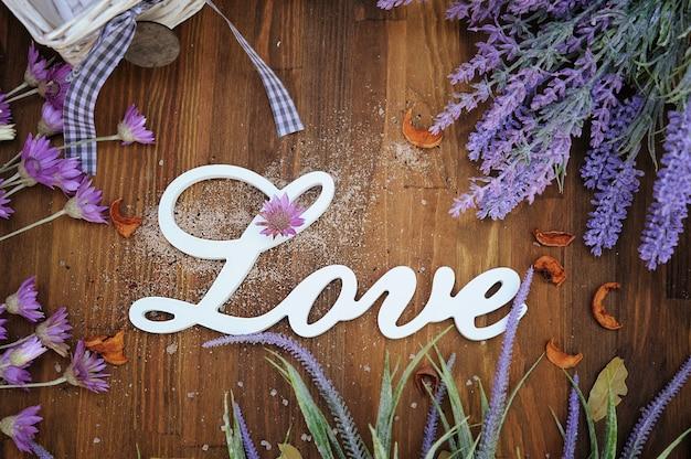Liebestext auf rustikalem holzhintergrund mit lavendel