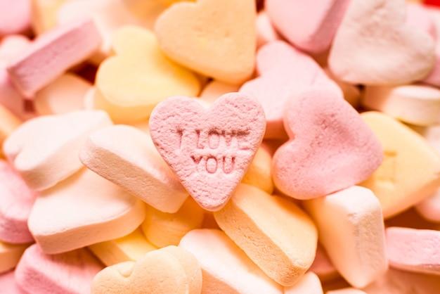 Liebeswort eingraviert in eine süße romantische herzförmige süßigkeit, um liebenden zu geben