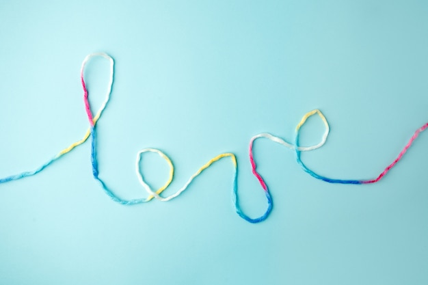 Liebeswort geschrieben mit garnbeschriftung, -konzept und -hintergrund für valentinstag