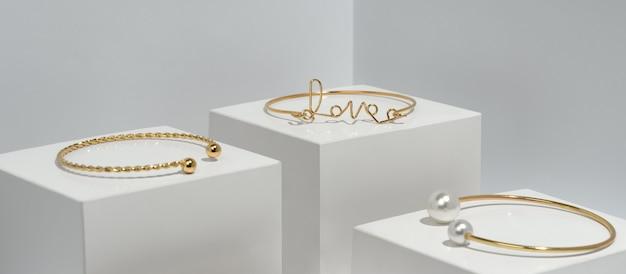 Liebeswort und goldenes armband mit perlen auf goldenen würfeln