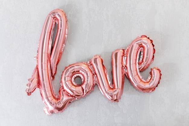 Liebeswort vom rosa aufblasbaren ballon auf grauem beton