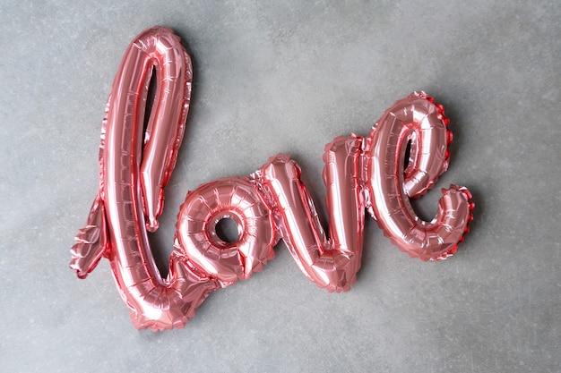 Liebeswort vom rosa aufblasbaren ballon auf grauem betonhintergrund. das konzept der romantik, valentinstag. liebe roségoldfolienballon