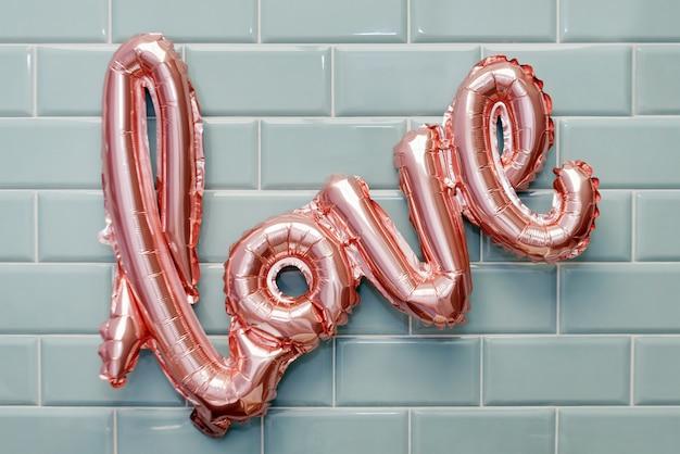 Liebeswort vom rosa aufblasbaren ballon auf minzefliesenwand