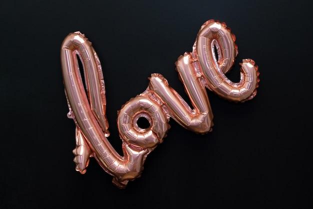 Liebeswort vom rosa aufblasbaren ballon auf schwarz lokalisiert auf schwarz