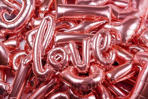 Liebeswort vom rosa aufblasbaren ballon, der auf anderen ballons liegt. das konzept der romantik, valentinstag. liebe roségoldfolienballon