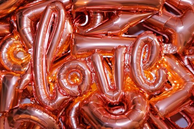 Liebeswort vom rosa aufblasbaren ballon, der auf anderen ballons liegt