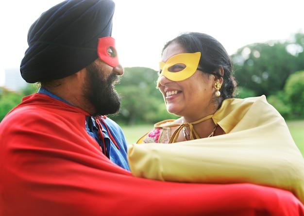 Liebevolle ältere indische paare, die superhelden spielen