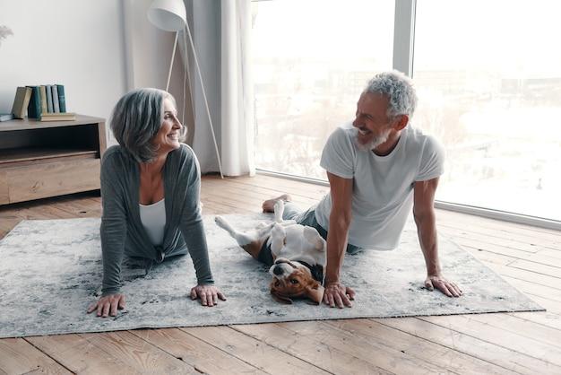 Liebevolle ältere paare in sportkleidung, die yoga machen und lächeln, während sie zeit zu hause mit ihrem hund verbringen