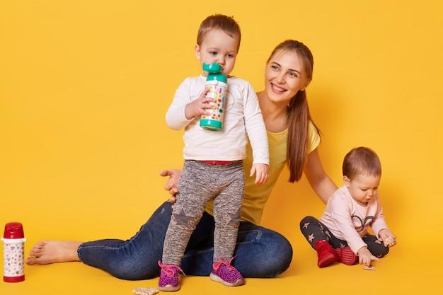 Liebevolle attraktive mutter kümmert sich um ihre kleinen kinder, zwillinge spielen mit mama. verspielte kinder trinken leckere zutaten aus ihrem bootle, während ihre schwester coockies isst. säuglinge haben hunger.