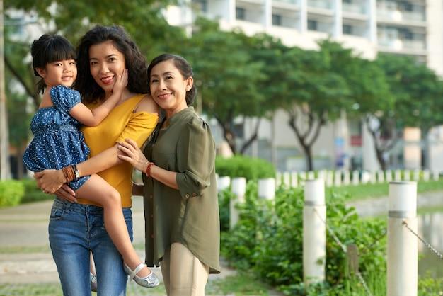 Liebevolle dreiköpfige familie, die für fotografie aufwirft