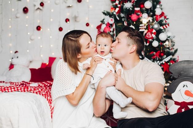 Liebevolle eltern mit kindern am weihnachten am verzierten tannenbaum.