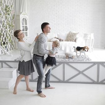Liebevolle eltern spielen mit der tochter im schlafzimmer