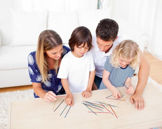 Liebevolle familie, die mikado im wohnzimmer spielt