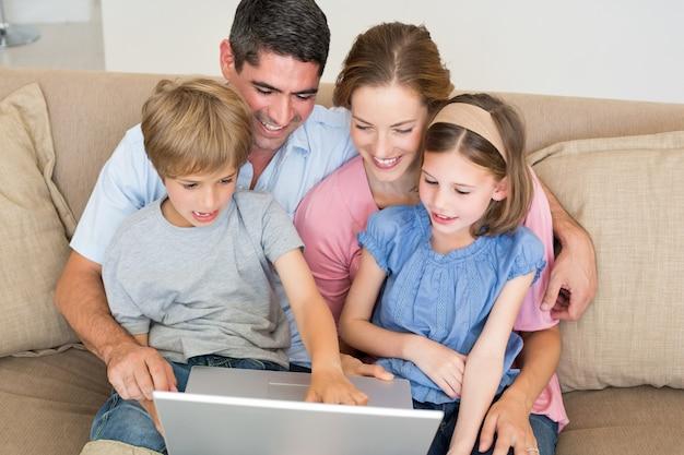 Liebevolle familie unter verwendung des laptops zusammen auf sofa