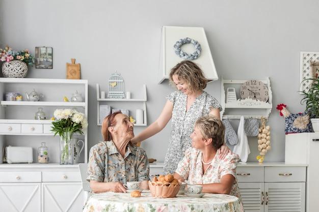 Liebevolle frauen aus drei generationen, die zu hause frühstücken