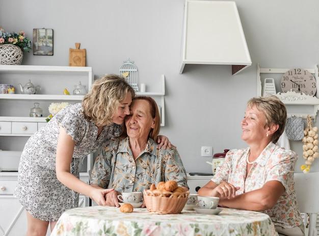 Liebevolle frauen der dritten generation, die zusammen frühstücken