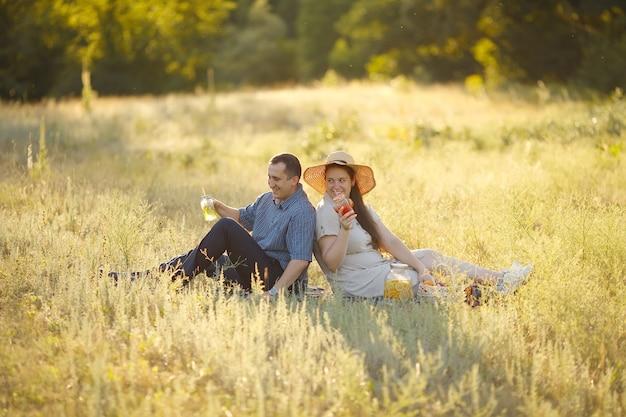 Liebevolle junge familie an einem wochenende picknick in der natur trinken saft aus gläsern mit strohhalmen