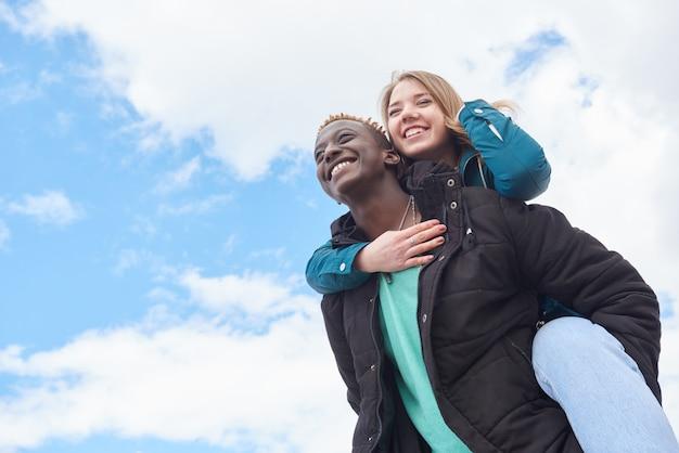 Liebevolle junge internationale paare auf himmel-hintergrund. afrikanischer kerl und kaukasische frau