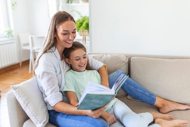 Liebevolle junge mutter, die ein buch für eine entzückende kleine tochter liest, auf einem gemütlichen sofa im wohnzimmer sitzt, eine mutter unterrichtet, die ein vorschulkind unterrichtet, eine familie, die ein wochenende zu hause zusammen verbringt, eine kindererziehung