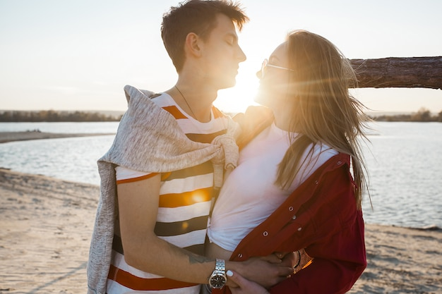 Liebevolle junge paare auf sonnenuntergang auf dem strand. liebe. mann und frau, die auf sommer küssen und umfassen.