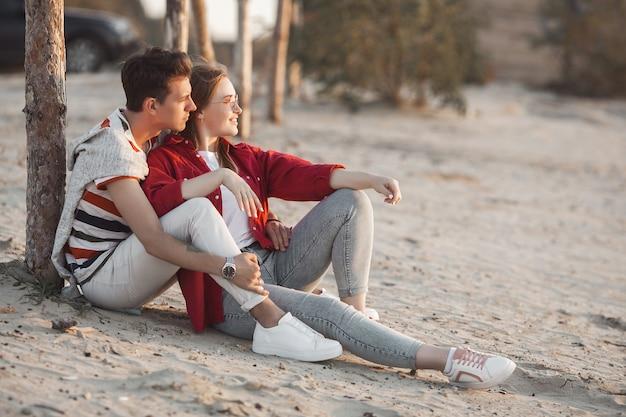 Liebevolle junge paare auf sonnenuntergang auf dem strand. liebe. mann und frau umarmen im sommer.