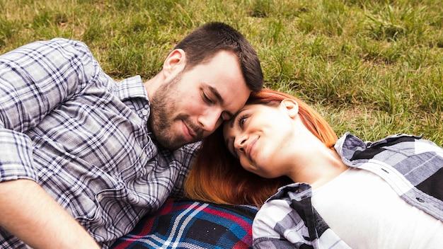 Liebevolle junge paare, die auf decke über grünem gras liegen