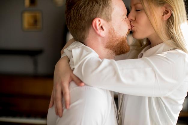 Liebevolle junge paare, die im raum küssen
