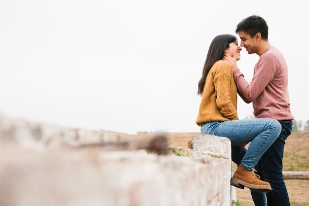 Liebevolle junge paare, die in der landschaft küssen