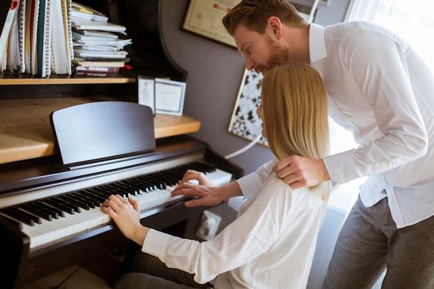 Liebevolle junge paare, die klavier spielen