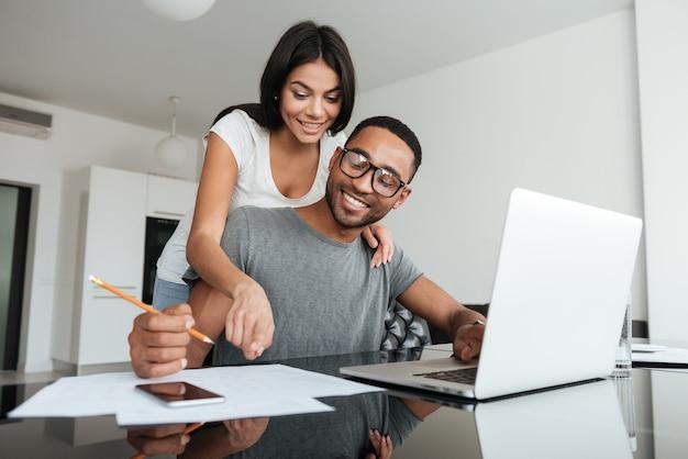 Liebevolle junge paare, die laptop verwenden und ihre finanzen analysieren. notizen schreiben.