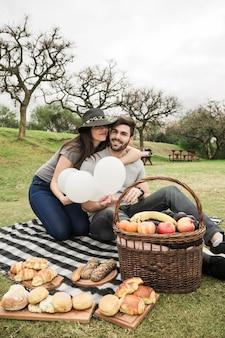 Liebevolle junge paare, die mit gebackenem lebensmittel und früchten über dem picknickkorb im park sitzen