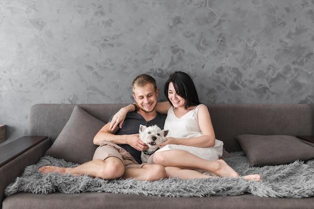 Liebevolle junge paare, die mit ihrem hund auf sofa gegen graue tapete sitzen