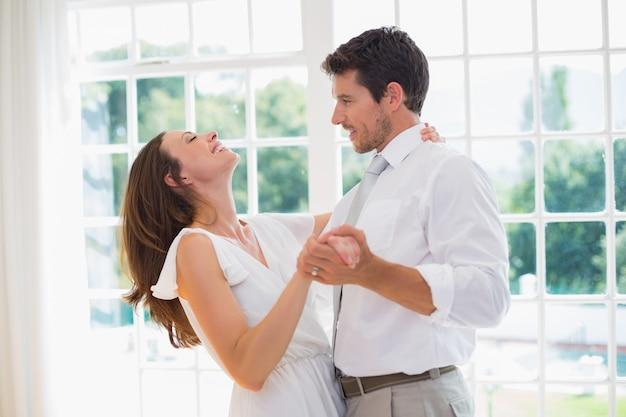Liebevolle junge paare, die zu hause tanzen