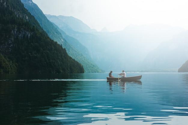 Liebevolle junge paare im boot am see. dattelwanderung mann und frau in alpinen bergen