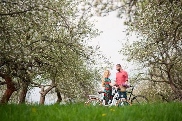 Liebevolle junge paare mit garten der fahrräder im frühjahr
