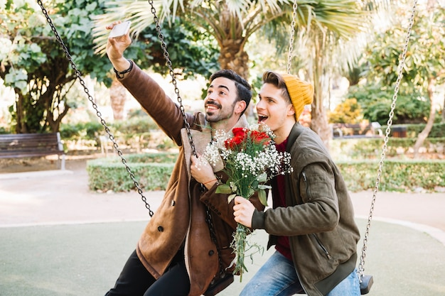 Liebevolle männer, die selfie mit blumenstrauß nehmen