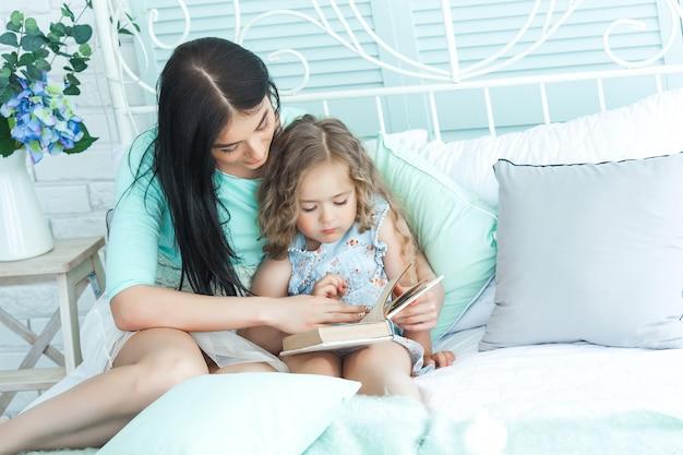 Liebevolle mutter, die ihrem kind eine gute-nacht-geschichte vorliest