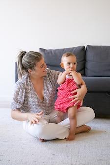 Liebevolle mutter, die mit gekreuzten beinen auf dem boden sitzt und baby ansieht. nettes kleines mädchen, das barfuß auf teppich nahe lächelnder mutter und beißende hände steht. familienzeit, mutterschaft und wochenendkonzept