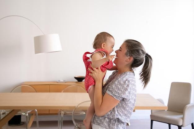 Liebevolle mutter hält tochter, lächelt und schaut sie an. glückliches kaukasisches süßes baby, das auf mutterhänden sitzt, spaß hat und lacht. familienzeit, mutterschaft und zuhause sein konzept